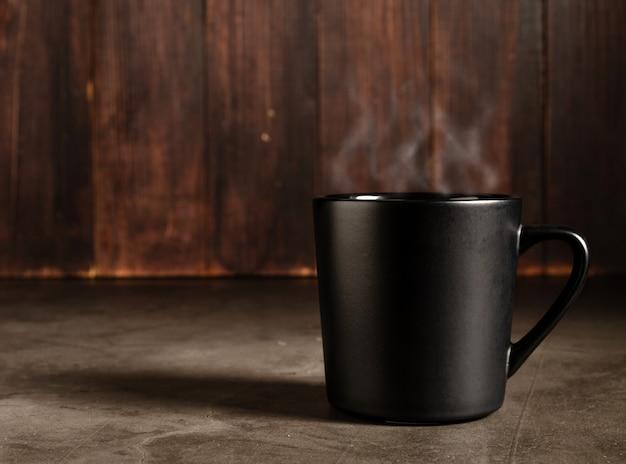 暗い木の背景と黒のマグカップでコーヒー Premium写真