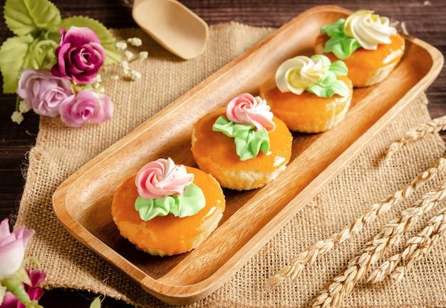 花と木製トレイ上のおいしいヴィンテージカップケーキ Premium写真