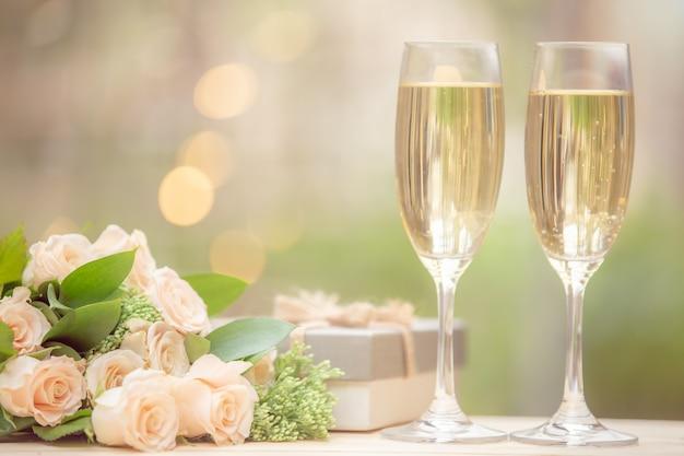 Цветок розы, подарочная коробка, бокал вина, на деревянном столе с боке Premium Фотографии