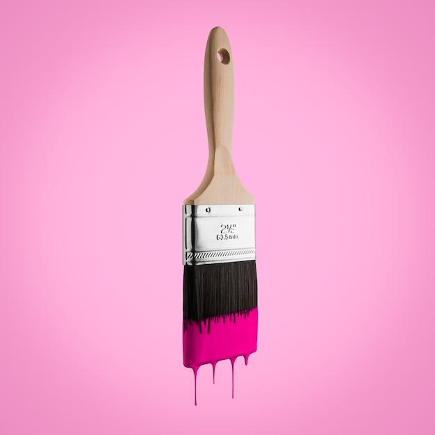 Кисть с розовым цветом капает с щетиной - изолированные на розовом фоне. Premium Фотографии