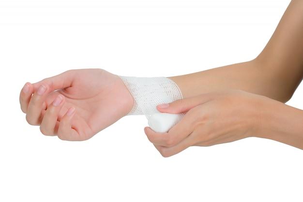 女性包帯救急彼女の手首を白で隔離される痛みの分野で Premium写真
