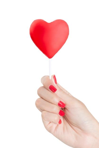 白い背景で隔離赤いハートロリポップを保持している赤い爪を持つ美しい女性手 Premium写真