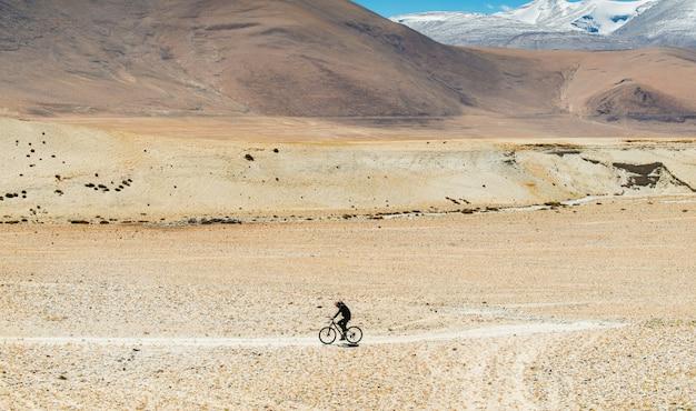 ヒマラヤ山脈の険しい道を通って男性サイクリスト Premium写真