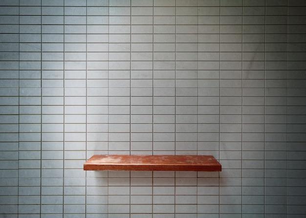 タイル壁に空の木製棚。 Premium写真