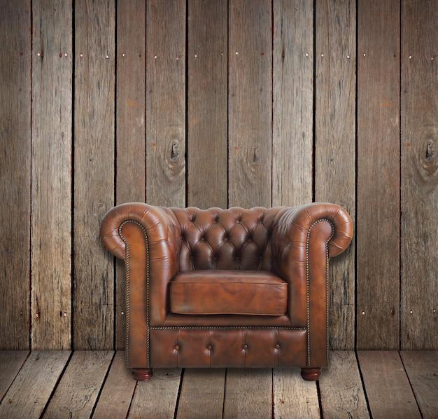 木製の部屋の古典的な茶色の革張りのアームチェア。 Premium写真