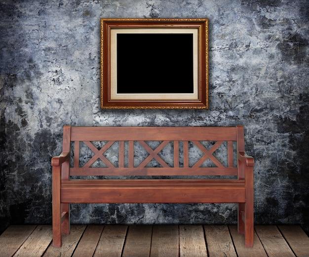汚れた壁にゴールドフレームと木製のベンチ。 Premium写真
