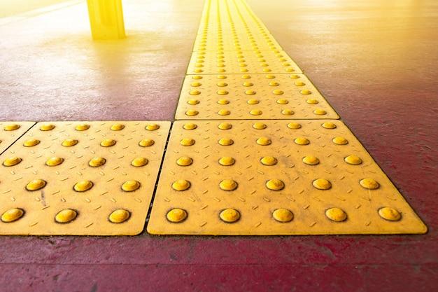 Грубое вымощение желтой точки тактильное для слепого гандикапа на пути плиток в японии, дорожке для людей слепоты. Premium Фотографии