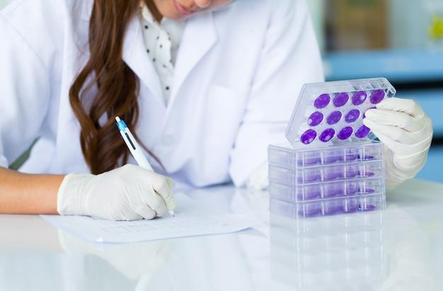 科学者の手は実験室でデング熱ウイルスのテストプレートを持っています。 Premium写真