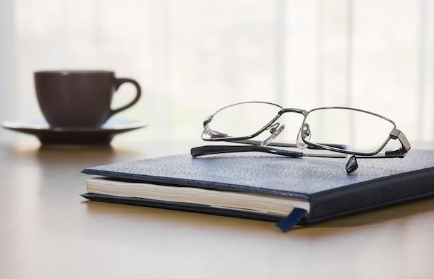 Очки и книга на столе Premium Фотографии