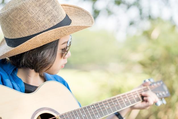 女性の身に着けている帽子とギターを弾く Premium写真