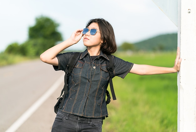 道路に沿ってヒッチハイクのバックパックを持つ女性スタンド Premium写真