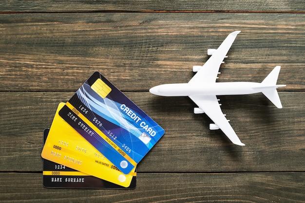 木製の机の上のクレジットカードと飛行機モデル Premium写真