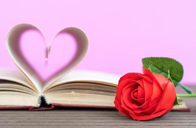 曲がったハートと赤いバラの本のページ Premium写真