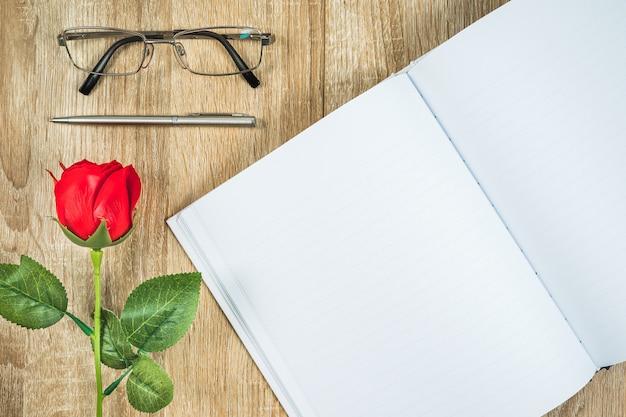 赤いバラバレンタインコンセプトと空白のノートブック日記 Premium写真