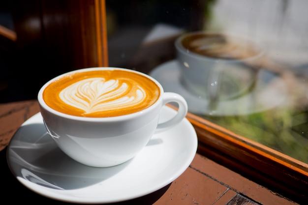木製テーブルの上のホットラテアートコーヒー、リラックスした時間 Premium写真