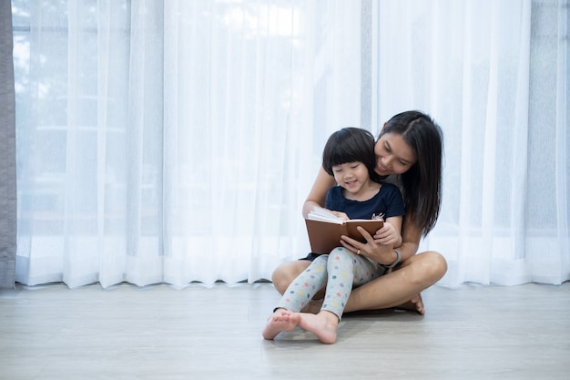 母はベッドで彼女の子供のための本を読んで、漫画の本を読んで、子供たちとお話 Premium写真