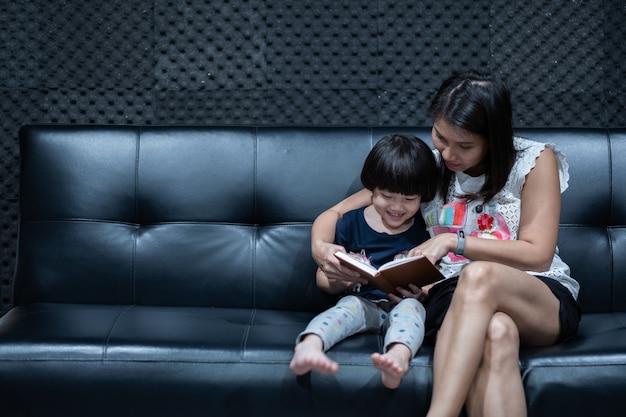 母はベッドで彼女の子供のための本を読んで、漫画本を読み、子供たちと語り Premium写真