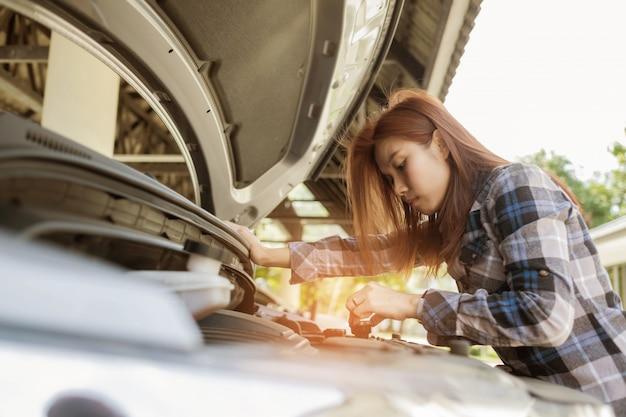 Женщина проверяет машину, меняет масло в машине Premium Фотографии