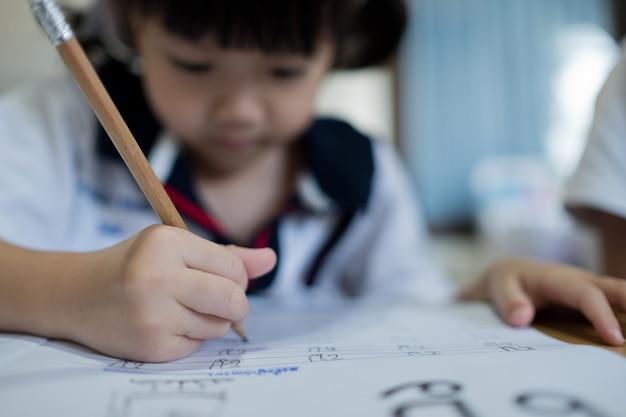 Дети девочка делает домашнее задание с матерью, ребенок пишет бумагу, концепция семьи, время обучения, студент, обратно в школу Premium Фотографии