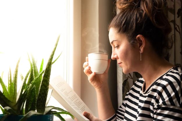 本を読んで、コーヒーやお茶を飲んで彼女のリビングルームでリラックスした自宅の窓の近くに座っている大人の白人女性 Premium写真