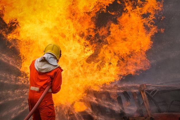 消防士は消火活動で水を使用しています Premium写真