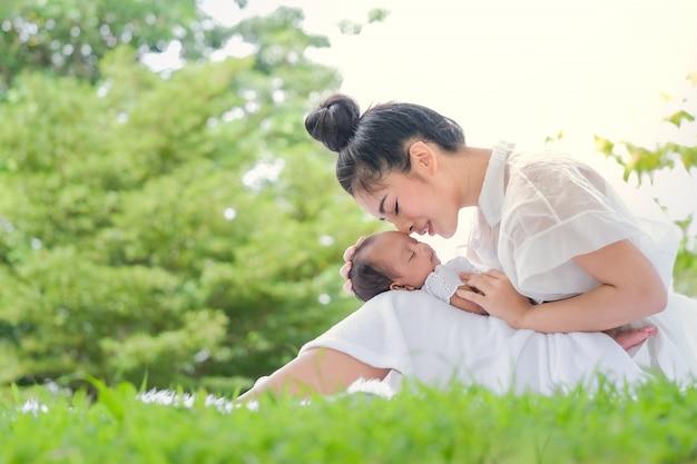 アジアの公園で美しい母親と赤ちゃん Premium写真