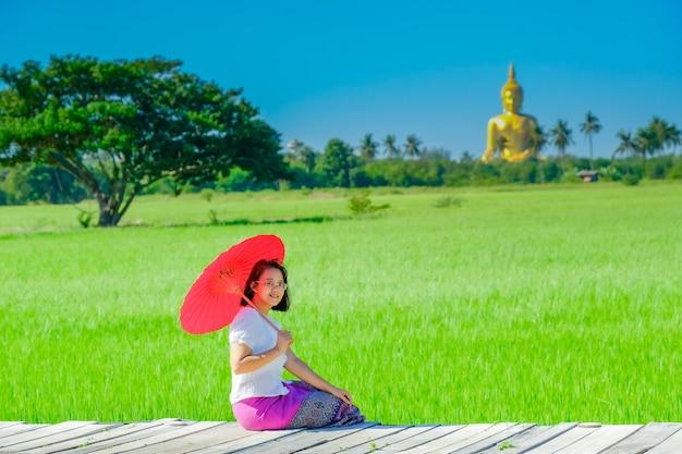 Азиатская женщина держа красный зонтик сидя на деревянном мосте в поле риса с большим золотым изображением будды. Premium Фотографии