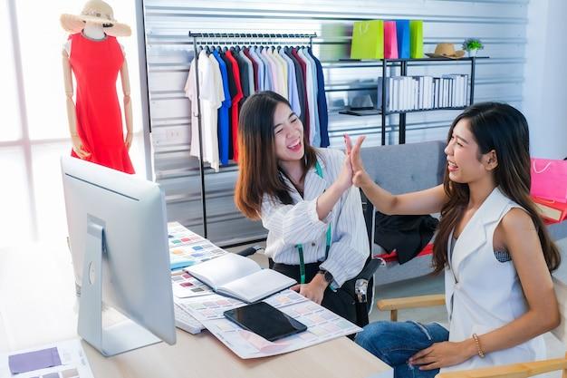 Азиатские женщины, которые работают модными дизайнерами и сшивают одежду на успешной работе. Premium Фотографии