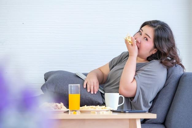太ったアジアの女性はフライドポテトを食べて楽しんでいます。 Premium写真
