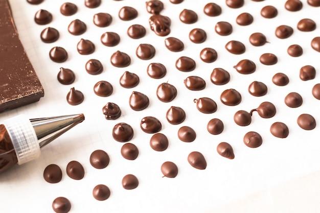 Концепция еды делает домашние шоколадные чипсы для пекарни на белом фоне Premium Фотографии