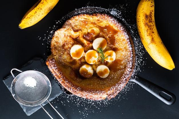 食品のコンセプト自家製ダッチベイビーバナナキャラメルトッピングフライパン鉄パンケーキブラックにキャスト Premium写真