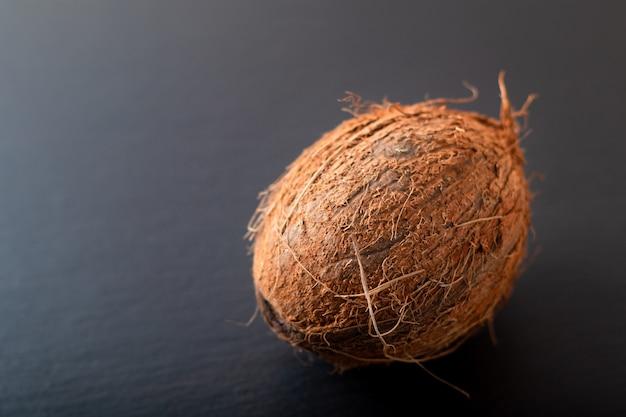 Весь один органический тропический кокосовый фрукт на черном сланце каменный фон с копией пространства Premium Фотографии