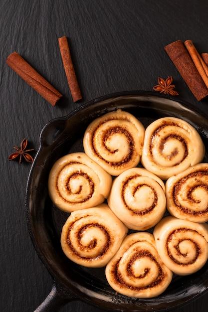 自家製シナモンロールの食品コンセプトふくらんでいるパン生地コピースペースを持つフライパン鋳鉄鍋で焼く前に調達 Premium写真