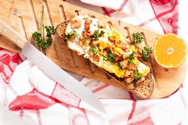 木製のまな板の上の卵とハムで焼いた食品コンセプト有機フレンチサワードウ Premium写真