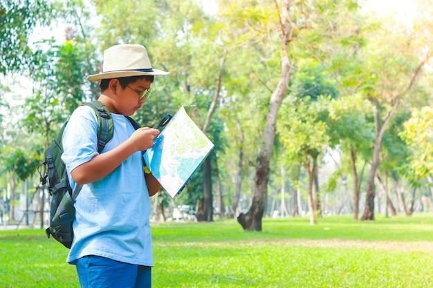 バックパックを運ぶ少年、地図を見る Premium写真