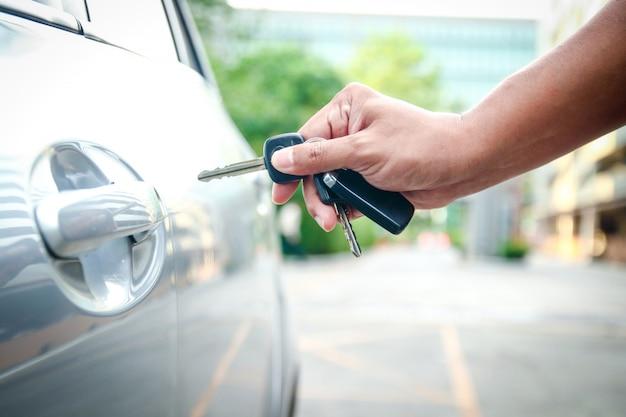 Мужская рука держит ключ, чтобы открыть дверь, чтобы открыть машину. Premium Фотографии