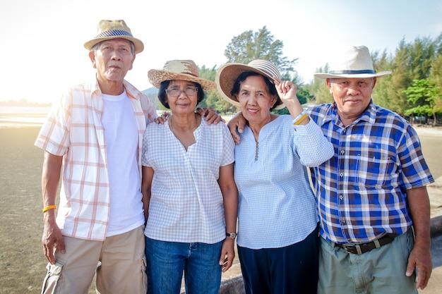 アジアの高齢者グループは、リラックスするために海を訪れます。 Premium写真
