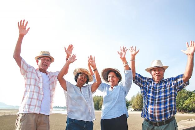 Пожилая группа мужчин и женщин в азии побывала на море. поднимите обе руки с удовольствием. Premium Фотографии