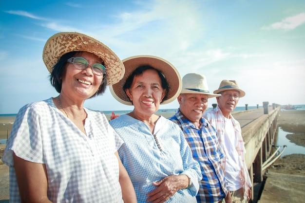 高齢者のアジア人グループは、海のそばのコンクリートの橋で笑顔で立ち、引退後は幸せです。 Premium写真