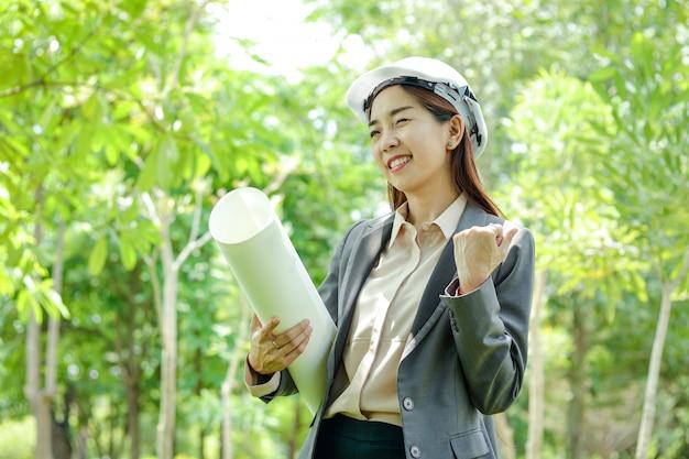 女性環境エンジニアは、紙製の帽子をかぶって、建設の実現可能性を研究しています。 Premium写真