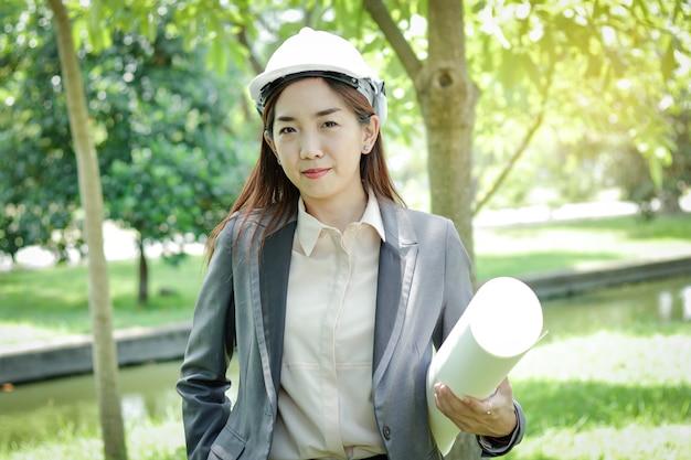 Женщины-инженеры-экологи носят шляпу с бумагой для изучения возможности строительства. Premium Фотографии
