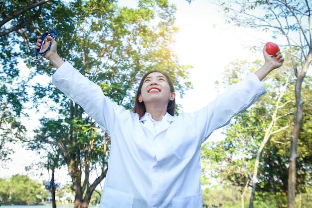 美しい女性医師は両手で両腕を伸ばし、赤いハートと聴診器を持って Premium写真