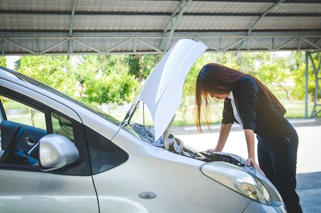 彼女はオフィスで仕事に急いでいたが、彼女の車が壊れている美しい女性 Premium写真