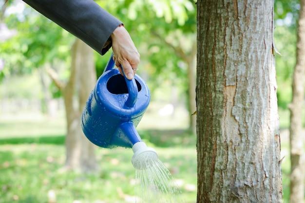 木を育てて強くするために、植物に水をまく缶を持ったビジネスマン。 Premium写真