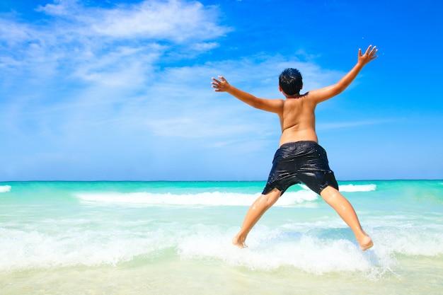 その少年はシャツを脱いでジャンプした。美しい海、白い砂浜、澄んだ水をプレーしに来てください。 Premium写真