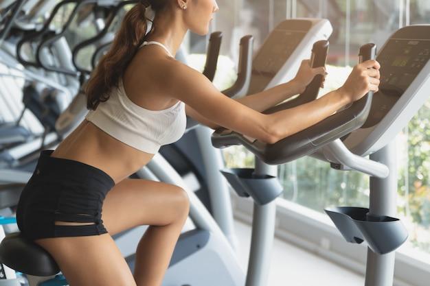 スポーツクラブで自転車のマシンで運動する女性。 Premium写真