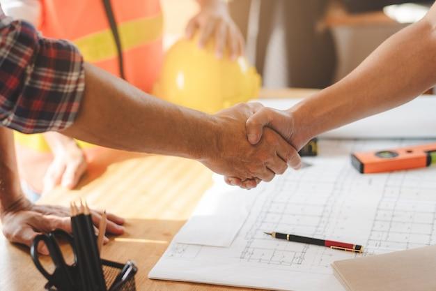 成功した取引、男性建築家が建物の改修工事のための青写真を確認した後、建設現場でクライアントと握手します。 Premium写真