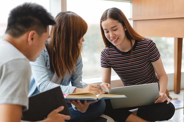 図書館で宿題のためのデータを研究しているアジアの学生のグループ。 Premium写真