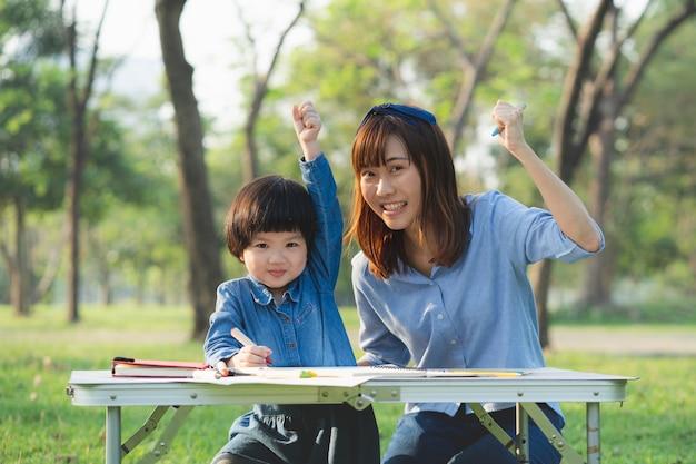 母と娘は休日に公園で絵を描きます。 Premium写真