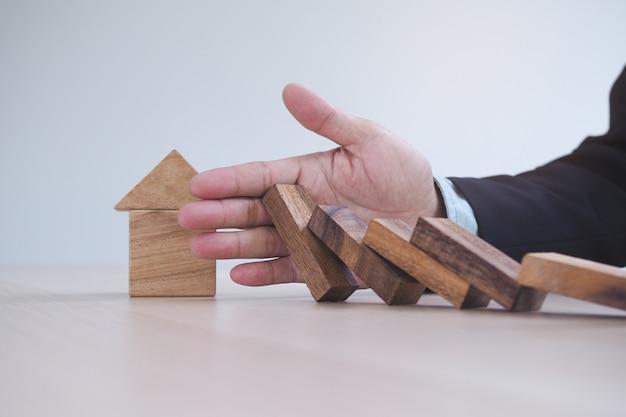 ドミノ効果の概念からの保護金融。手は家を破壊する前にドミノ効果を停止します。 Premium写真